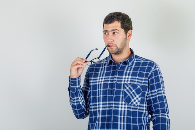 Jeune homme en chemise à carreaux mordre les verres et à la réflexion