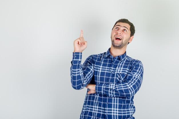 Jeune homme en chemise à carreaux pointant le doigt vers le haut et à la