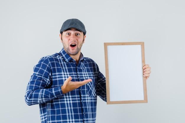 Jeune homme en chemise, casquette montrant un cadre vide et regardant étonné, vue de face.