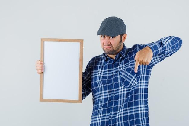 Jeune homme en chemise, casquette tenant un cadre vide, pointant vers le bas et à la vue douteuse, de face.
