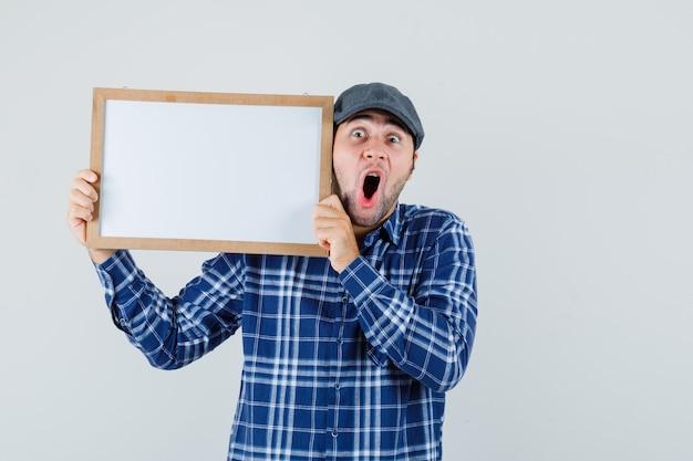 Jeune homme en chemise, casquette tenant un cadre vide et regardant choqué, vue de face.