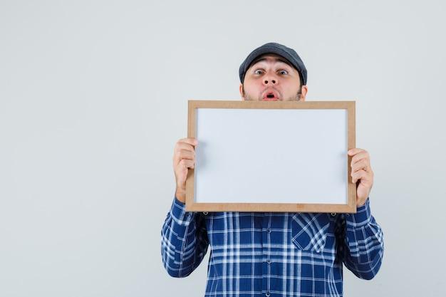 Jeune homme en chemise, casquette tenant un cadre vide et regardant étonné, vue de face.
