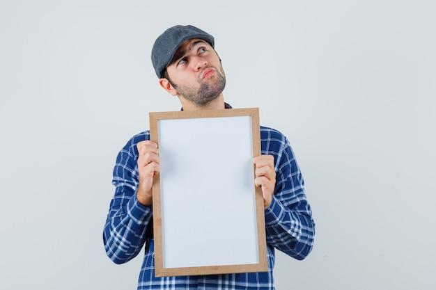 Jeune homme en chemise, casquette tenant un cadre vide et regardant pensif, vue de face.