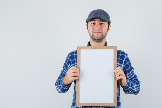 Jeune homme en chemise, casquette tenant un cadre vide et à la vue de face, confiant.