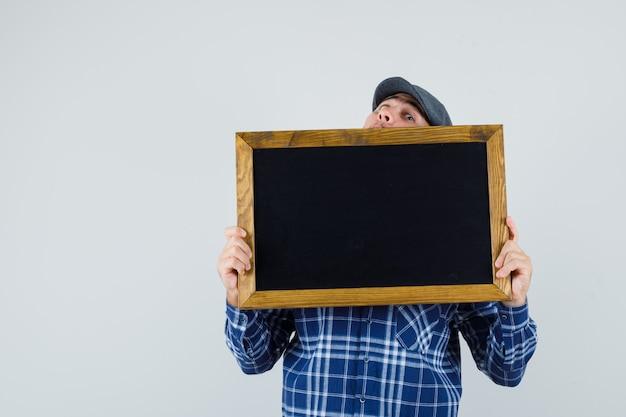 Jeune homme en chemise, casquette tenant tableau noir et à la surprise, vue de face.