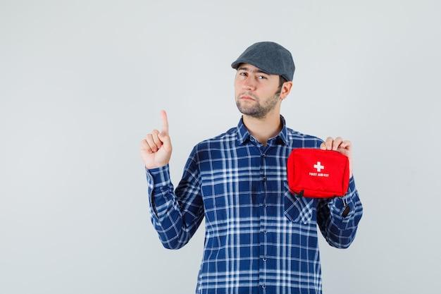 Jeune homme en chemise, casquette tenant une trousse de premiers soins, pointant vers le haut et regardant pensif, vue de face.