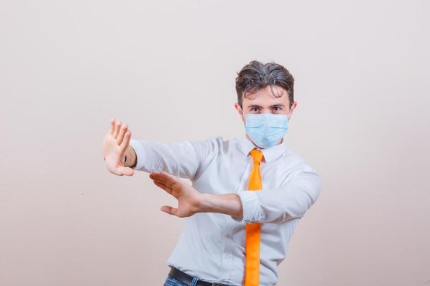 Jeune homme en chemise, cravate, masque gardant les mains pour se défendre et ayant l'air effrayé