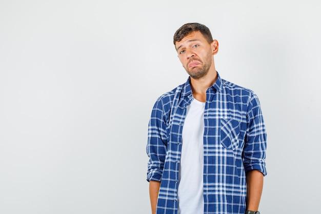 Jeune homme en chemise debout et regardant et regardant triste, vue de face.