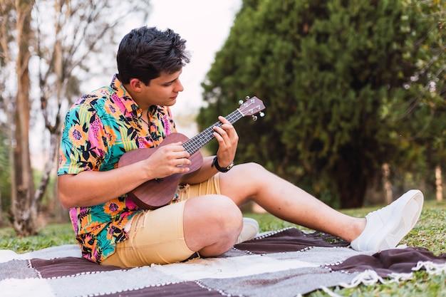 Jeune homme avec chemise fleurie jouant de la guitare ukulélé assis dans le jardin.