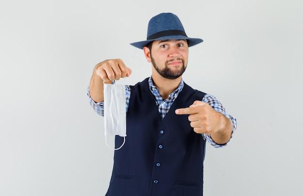 Jeune homme en chemise, gilet, chapeau pointant sur un masque médical et à l'optimiste, vue de face.