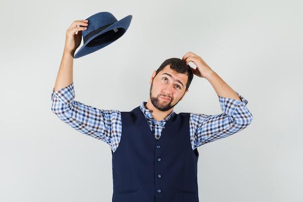 Jeune homme en chemise, gilet décoller son chapeau, se gratter la tête et à la pensif