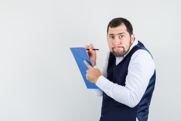 Jeune homme en chemise, gilet en prenant des notes sur le presse-papiers et à la perplexité, vue de face.