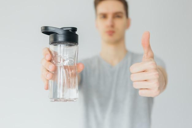 Jeune homme en chemise grise de l'eau potable pendant le sport. le sport à la maison. homme sur fond gris