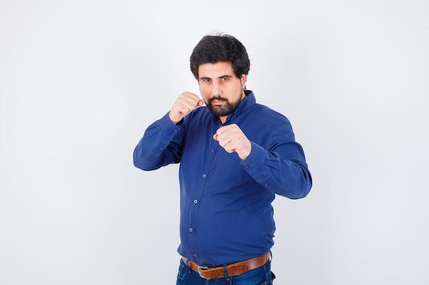 Jeune homme en chemise, jeans debout dans la pose de combat et à la rancune, vue de face.