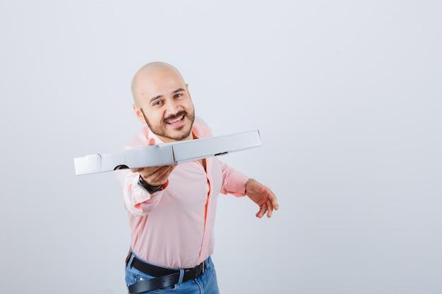 Jeune homme en chemise, jeans montrant le geste de donner et l'air optimiste, vue de face.
