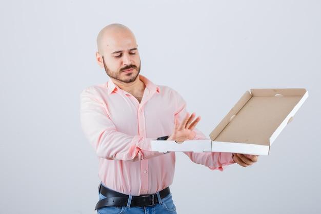 Jeune homme en chemise, jeans montrant un geste de refus et l'air confiant, vue de face.