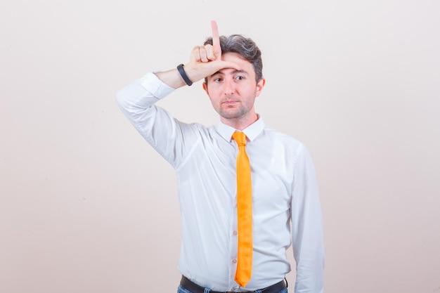 Jeune homme en chemise, jeans montrant le signe du perdant sur le front