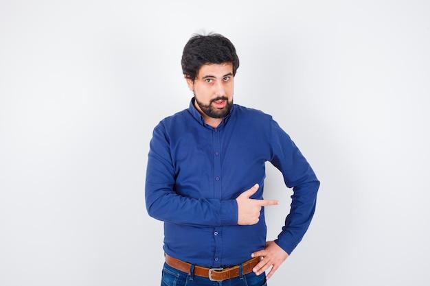 Jeune homme en chemise, jeans pointant vers le côté droit et semblant positif, vue de face.