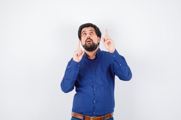 Jeune homme en chemise, jeans pointant vers le haut et l'air étonné, vue de face.