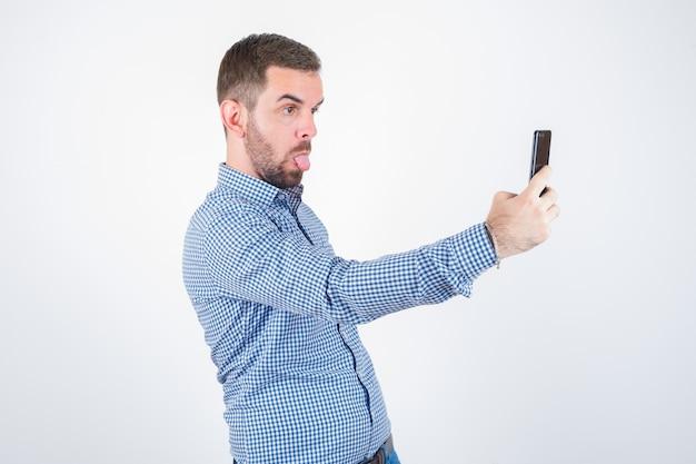 Jeune homme en chemise, jeans prenant un selfie tout en sortant la langue et à la drôle, vue de face.