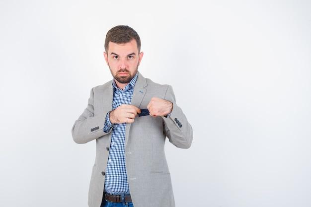 Jeune homme en chemise, jeans, veste de costume gardant un mouchoir de poche et à la vue de face, confiant.