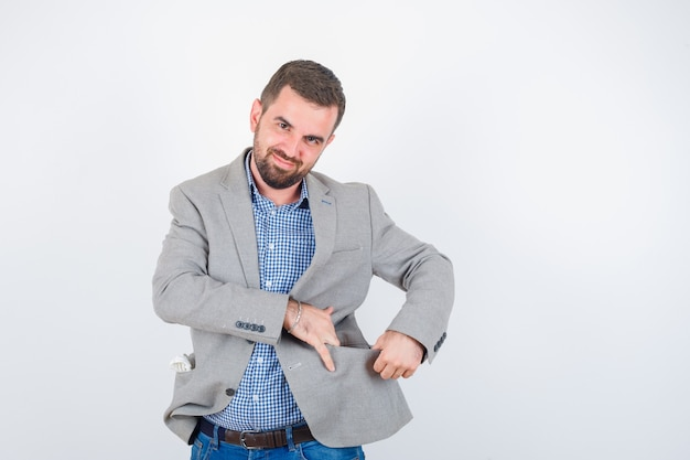 Jeune homme en chemise, jeans, veste de costume, ouverture de la poche de la veste avec les mains et à la joyeuse, vue de face.