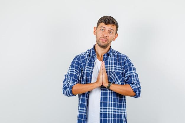 Jeune homme en chemise, main dans la main en signe de prière et à la triste, vue de face.