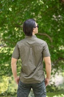 Jeune homme en chemise à manches courtes et pantalon debout dans le parc