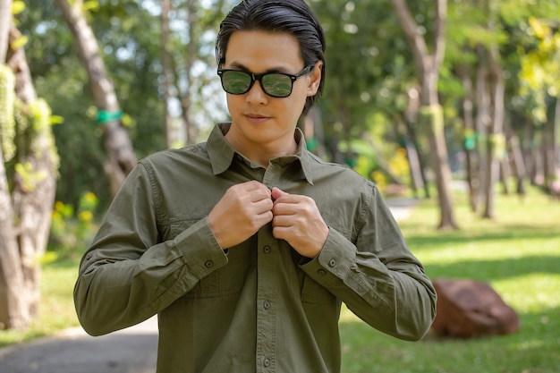 Jeune homme en chemise à manches longues vert debout dans le parc