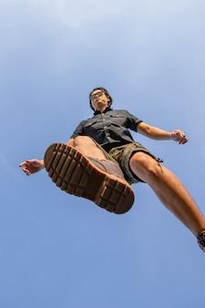Jeune homme en chemise à manches et pantalon cargo court debout dans le parc