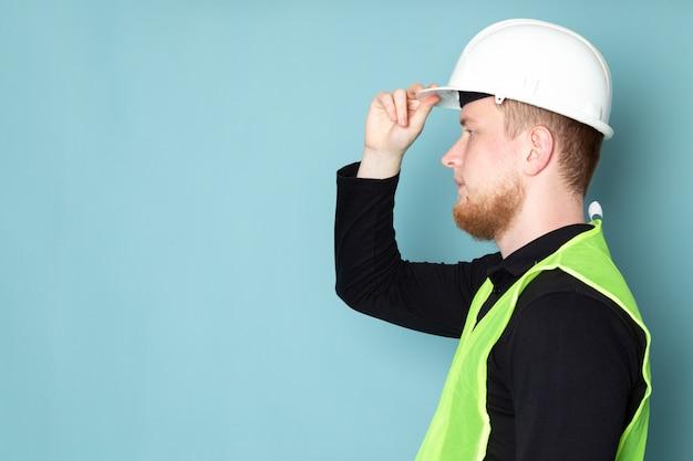 Jeune homme en chemise noire et gilet de construction vert