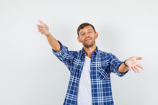 Jeune homme en chemise ouvrant les bras larges comme accepter quelque chose et regarder joyeux, vue de face.