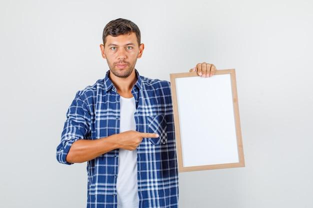 Jeune homme en chemise pointant le doigt au tableau blanc et à la grave, vue de face.