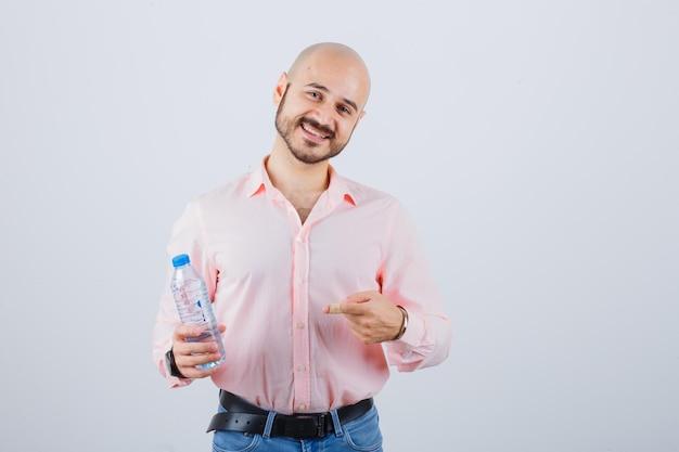 Jeune homme en chemise rose, jeans tenant une bouteille d'eau tout en pointant dessus et en regardant joyeux, vue de face.
