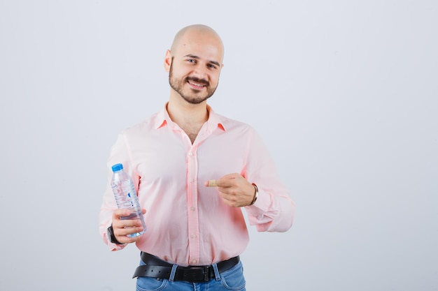 Jeune homme en chemise rose, jeans tenant une bouteille d'eau tout en le pointant, vue de face.