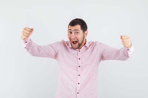 Jeune homme en chemise rose montrant le geste du gagnant et l'air heureux
