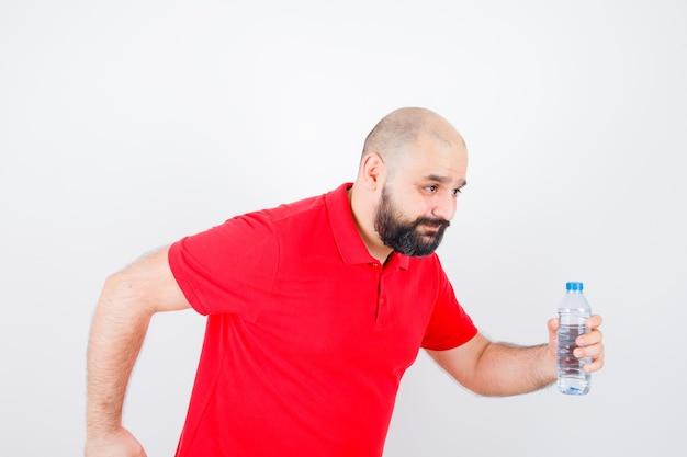 Jeune homme en chemise rouge courant tout en tenant une bouteille et en regardant à la hâte.