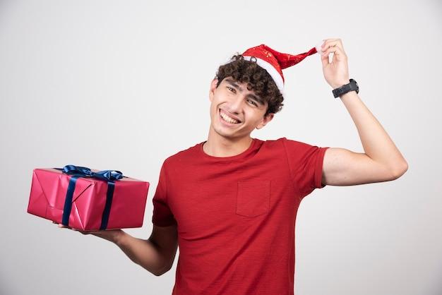 Jeune homme en chemise rouge touchant son chapeau.