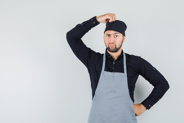 Jeune homme en chemise, tablier se gratter la tête avec la main sur la taille et regardant pensif, vue de face.