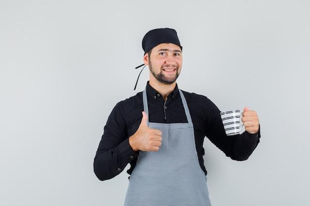 Jeune homme en chemise, tablier tenant une tasse de boisson avec le pouce vers le haut et à l'optimiste, vue de face.
