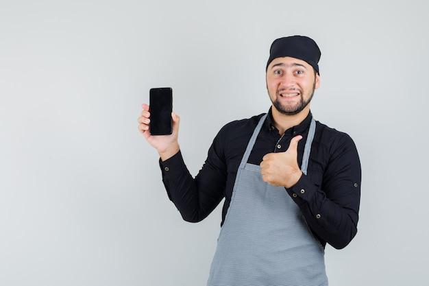 Jeune homme en chemise, tablier tenant le téléphone mobile avec le pouce vers le haut et à la vue de face, heureux.