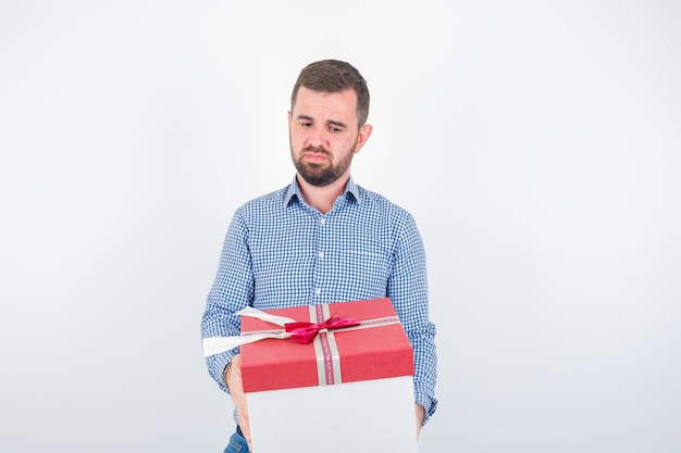 Jeune homme en chemise tenant une boîte-cadeau et à la déçu, vue de face.