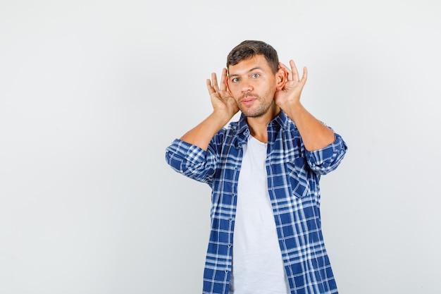 Jeune homme en chemise tenant les mains derrière les oreilles et à la ruse, vue de face.