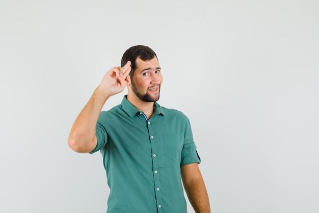 Jeune homme en chemise verte montrant un geste d'adieu et l'air calme, vue de face.