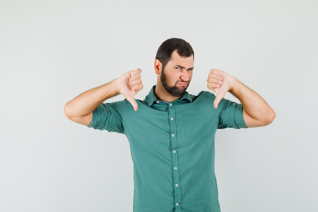 Jeune homme en chemise verte montrant le pouce vers le bas et l'air insatisfait, vue de face.