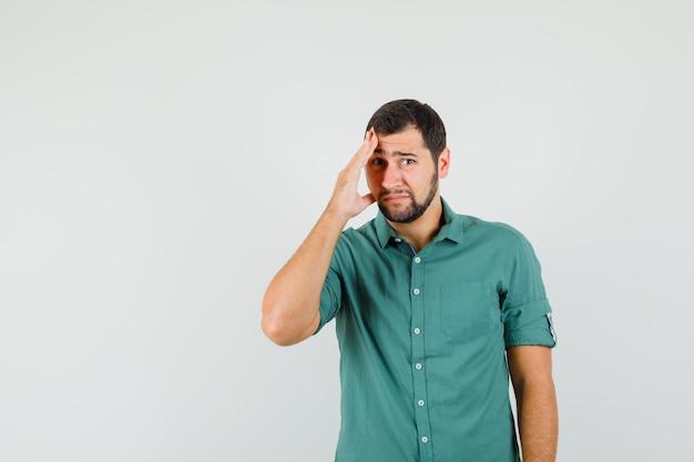 Jeune homme en chemise verte tenant les mains sur son visage et l'air inquiet, vue de face.