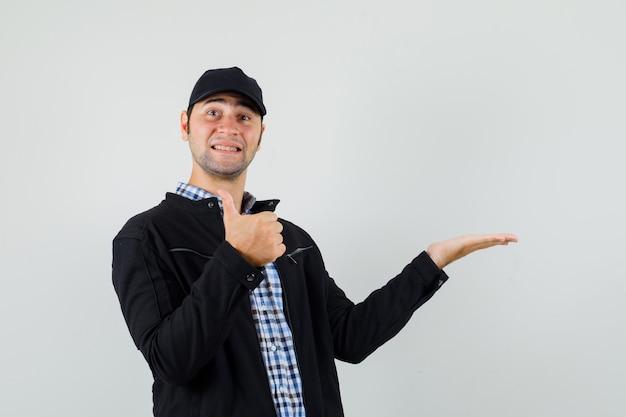 Jeune homme en chemise, veste, casquette écartant la paume de côté, montrant le pouce vers le haut et à la bonne humeur