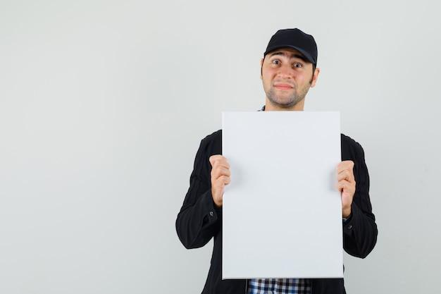 Jeune homme en chemise, veste, casquette tenant une toile vierge et à l'optimisme