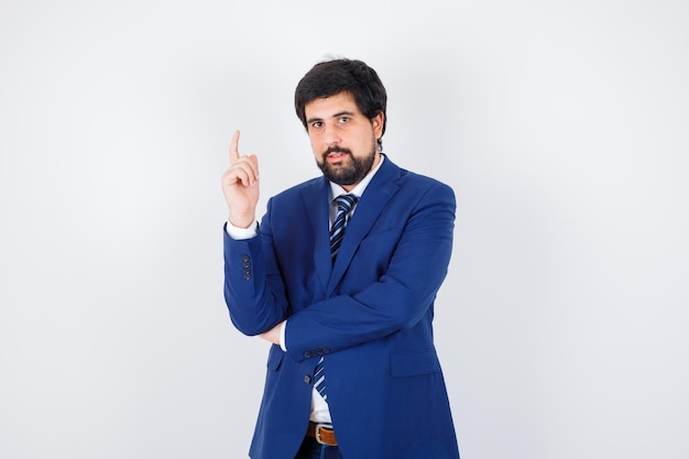 Jeune homme en chemise, veste, cravate pointant vers le haut et semblant sérieux, vue de face.
