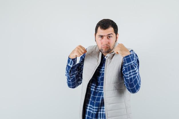 Jeune homme en chemise, veste levant les poings et regardant prêt, vue de face.